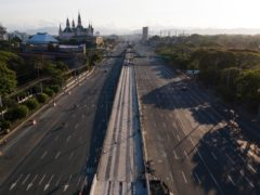 Motorist traverse an almost empty Commonwealth Avenue as the government implements a strict lockdown to prevent the spread of coronavirus in Quezon city, Philippines (Aaron Favila/AP)