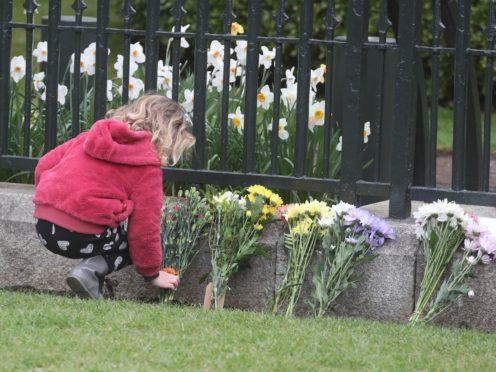 A girl leaves flowers outside Windsor Castle on Saturday (Steve Parsons/PA)