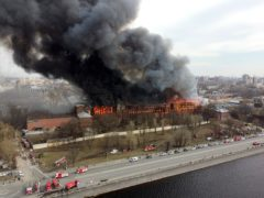 Smoke and flames rise from a building in St Petersburg, Russia (Dmitri Lovetsky/AP)
