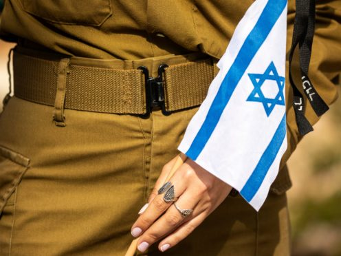 An Israeli soldier holds a flag with black ribbon attached to it as she stands by an Israeli soldier's grave ahead of the country's memorial day for fallen soldiers and victims of attacks, at the Kiryat Shaul Military Cemetery in Tel Aviv, Israel, Tuesday, April 13, 2021. Memorial Day begins at dusk on Tuesday and lasts until Wednesday evening. (AP Photo/Ariel Schalit)