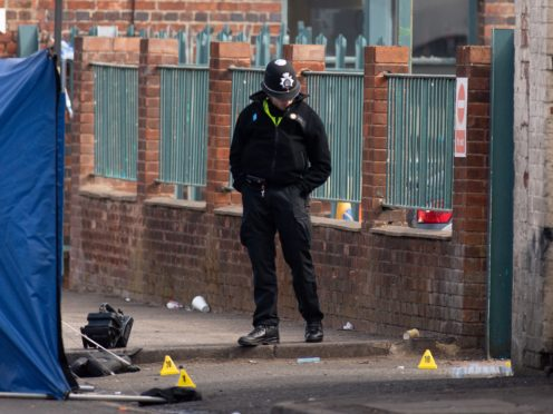 A police officer inspects the scene at an industrial premises on Western Road near Birmingham's City Hospital where a murder investigation has been launched after a fatal shooting (Jacob King/PA)