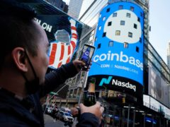 Coinbase employee Daniel Huynh holds a celebratory bottle of champagne as he photographs outside the Nasdaq MarketSite (Richard Drew/AP)