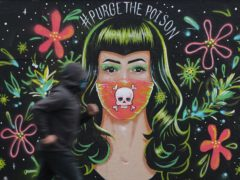 A jogger passes a mural by Brazilian artist Gabriel Marques in Dublin's Grand Canal area, during Covid-19 lockdown (Niall Carson/PA)