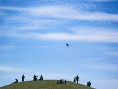 A man flies a kite during the warm weather on a hill at Northala Fields in west London (Victoria Jones/PA)