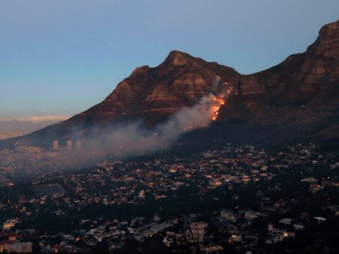 Fire burns on the slopes of Table Mountain in Cape Town, South Africa, Monday, April 19, 2021. People were evacuated from Cape Town neighbourhoods as a raging wildfire sweeping across the slopes of the city's famed Table Mountain was fanned by high winds and threatened homes. City authorities said the fire, which started early Sunday, was still not under control. The blaze has already burned the library and other buildings on the campus of the University of Cape Town. (AP Photo/Nardus Engelbrecht)