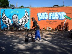 A man walks past a mural in the Houston neighbourhood where George Floyd grew up on Tuesday (David J Phillip/AP)