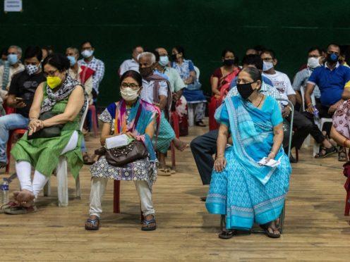 People wait to receive a coronavirus vaccine at an indoor stadium in Gauhati (AP)