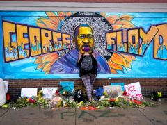 A woman pays her respects at George Floyd at a mural at George Floyd Square in Minneapolis. An application has been lodged to pardon a 2004 drugs conviction against Mr Floyd (Julio Cortez/AP)