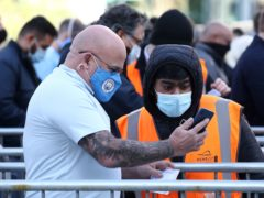A Manchester City fan shows a Covid-19 test result to a steward outside the Wembley stadium ahead of the Carabao Cup Final (Gareth Fuller/PA)