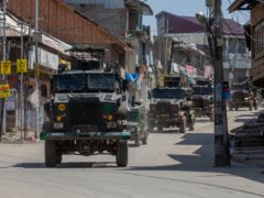 Indian army vehicles leave after a gun battle in Shopian, south of Srinagar, in Indian-controlled Kashmir on Friday (Dar Yasin/AP)