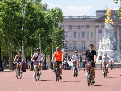 Cyclists ride along the Mall, as people enjoy the good weather in London. (Dominic Lipinski/PA)