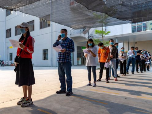 Residents wearing masks line up for a Covid-19 vaccination at the Jingcheng Hospital in Ruili (Chen Xinbo/Xinhua via AP)