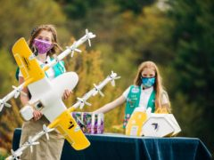 Girl Scouts Alice Goerlich and Gracie Walker pose with a Wing delivery drone (Sam Dean/ Wing LLC via AP)