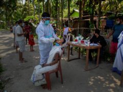 A health worker takes the swab of a woman to test for Covid-19 in Burha Mayong village in the Morigaon district of Assam (Anupam Nath/AP/PA)