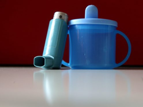 An inhaler used for treating asthma sits beside a child's cup (Brian Lawless/PA)