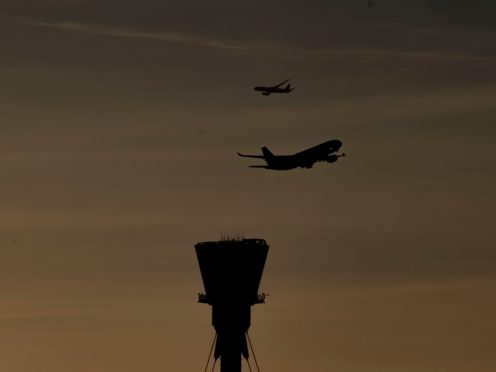 A plane takes off past the control tower at Heathrow Airport (Steve Parsons/PA)