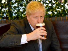Prime Minister Boris Johnson sips a pint in a beer garden (PA)