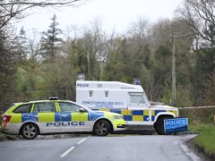 Police attending the scene last month after a bomb was discovered beside a car belonging to a police officer in Co Londonderry (Niall Carson/PA)