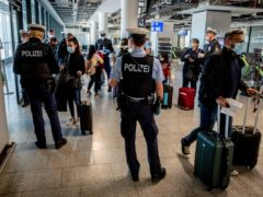 German police check passengers arriving from Mallorca for a negative Covid test as they arrive in Frankfurt (Michael Probst/AP)