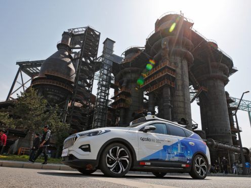 A Baidu Apollo Robotaxi move past a steel plant at the Shougang Park in Beijing, Sunday, May 2, 2021. Chinese tech giant Baidu rolled out its paid driverless taxi service on Sunday, making it the first company that commercialized autonomous driving operations in China. (AP Photo/Andy Wong)