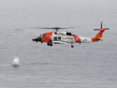 A US Coast Guard helicopter flies over boats searching the area where a boat capsized just off the San Diego coast (Denis Poroy/AP)