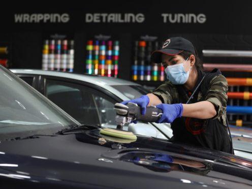 Iranian car detailer Maryam Roohani polishes a car at a detailing shop in Tehran (Vahid Salemi/AP)