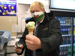 Prime Minister Boris Johnson holds an ice cream during a visit to Marco's Cafe in Barry Island (Matthew Horwood/PA)