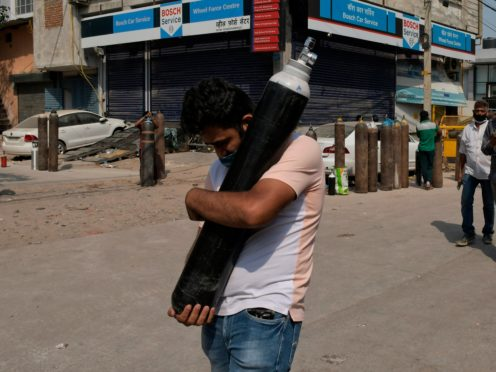 A man walks carrying a refilled cylinder as family members of Covid-19 patients wait in queue to refill their oxygen cylinders at Mayapuri area in New Delhi, India (Ishant Chauhan/AP)