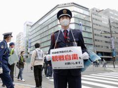 A security guard stands with a note calling for refraining from watching a half-marathon in Sapporo (Kyodo/AP)