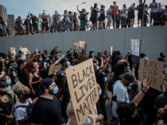 Protesters march on Brooklyn Bridge in New York following the death of George Floyd (John Minchillo/AP)