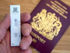 A person holds a negative Covid-19 test in front of a passport (Andrew Matthews/PA)