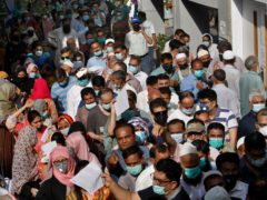 People queue up to receive their first dose of the Sinopharm Covid-19 vaccine in Karachi, Pakistan (Fareed Khan/AP)