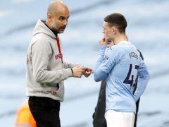 Pep Guardiola, left, speaks to Phil Foden (Martin Rickett/PA)