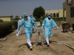 Doctors caring for Covid-19 patients in Chad carry medical equipment (Sunday Alamba/AP)