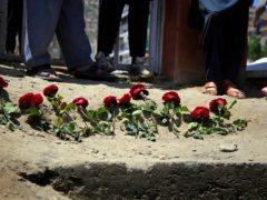 People puts flowers outside a school after a deadly attack on Saturday, in Kabul, Afghanistan (Mariam Zuhaib/AP)