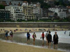 People walk along La Concha beach in San Sebastian, northern Spain (Alvaro Barrientos/AP)