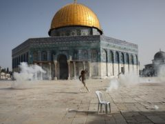 A Palestinian man runs away from tear gas during clashes with Israeli security forces in front of the Dome of the Rock Mosque at the Al Aqsa Mosque compound in Jerusalem's Old City (Mahmoud Illean/AP)