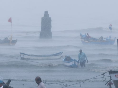 A fisherman waits for help as he tries to move a boat to safer ground (Rafiq Maqbool/AP)