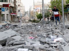 A man stands amid the rubble following an Israeli air strike in Gaza City (Adel Hana/AP)