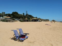 Two chairs rest on the sand at a nearly empty beach in Albufeira, in Portugal's southern Algarve region (Ana Brigida/AP)