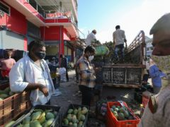 Workers unload fruits at a market during the relaxation hours of a lockdown to curb the spread of Covid-19 in Bengaluru, India (Aljaz Rahi/AP)