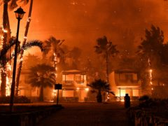 A wildfire burns houses in Greece (Valerie Gache/AP)