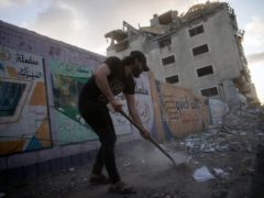 People clean the streets of debris beside a building that was previously damaged in an air strike in Gaza City (AP)