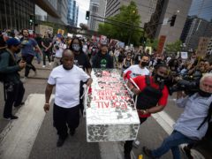 People carry a symbolic casket a rally and march for the first anniversary of George Floyd's death in Minneapolis (AP)