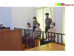 In this image from Myawaddy TV, a photograph shown during a news report showing the appearance of deposed Myanmar leader Aung San Suu Kyi, former president Win Myint, sitting 3rd from right, and former Naypyitaw Council chairman Dr. Myo Aung before a special court, shown while a report about Suu Kyi's case is read by a news presenter in Naypyitaw, Myanmar (Myawaddy TV via AP)