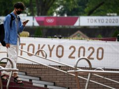 A man wearing a mask to help protect against the spread of the coronavirus walks near banners promoting the Tokyo Olympic Games Tuesday, May 25, 2021, in Tokyo. (AP Photo/Eugene Hoshiko)