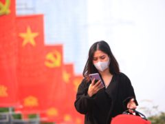 A woman wearing face mask looks at her phone in Hanoi (AP)