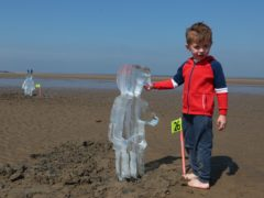 Toby Heptinstall, three, looks at one of 26 ice sculptures of children installed on New Brighton Beach, Wallasey in Merseyside (Peter Byrne/PA)