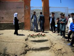 People puts flowers outside the school (Mariam Zuhaib/AP/PA)