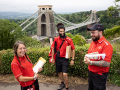 Andrea Clark, Chay Jackson and Ant Thornton are pictured in their new uniform against the backdrop of Clifton Suspension Bridge, in Bristol (Royal Mail/PA)